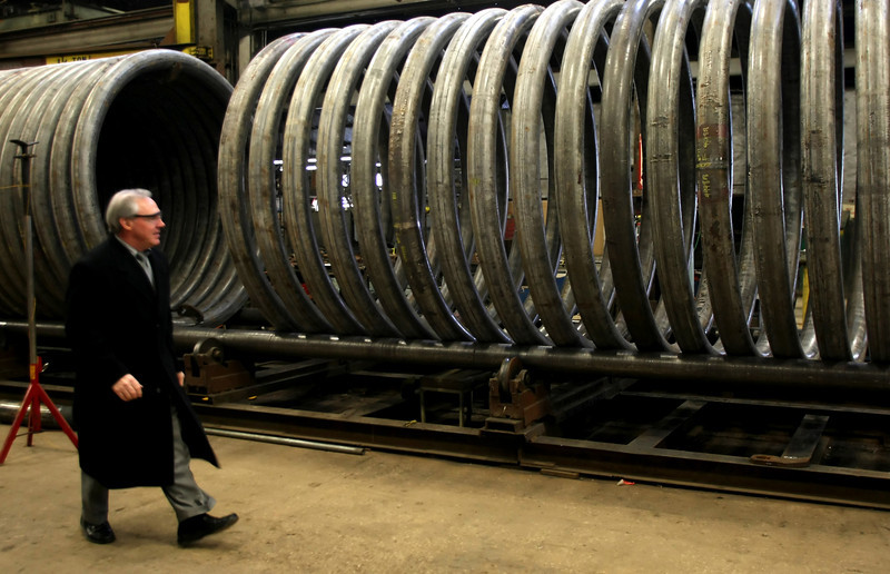 Larry Houston, President of American Pipe Bending Company,  inspects a section of a large heating coil being produced at the Tulsa company.
