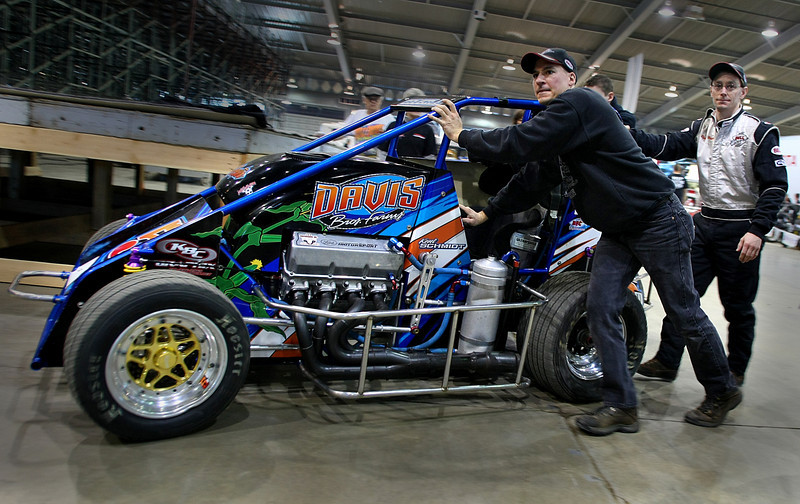 Crew members push race car to the starting grid at the Chili Bowl midget race Monday.  The week long racing event at the Tulsa fairgrounds brings millions of dollars of revenue into the Tulsa economy each year.