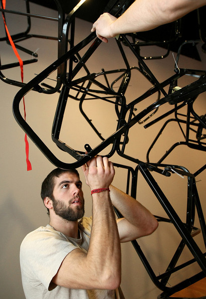 Oklahoma University sculpture and painting student Mick Trisemer installs a Jason Peters sculpture at the Oklahoma Museum of Art Monday. PHOTO BY MAIKE SABOLICH