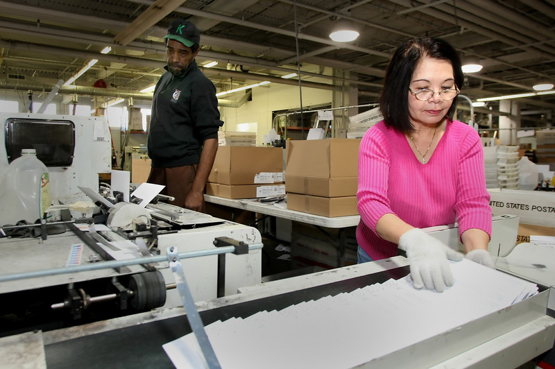 David Lewis and Cuz Nguyen sort mailers at the central Tulsa location of Resource One.
