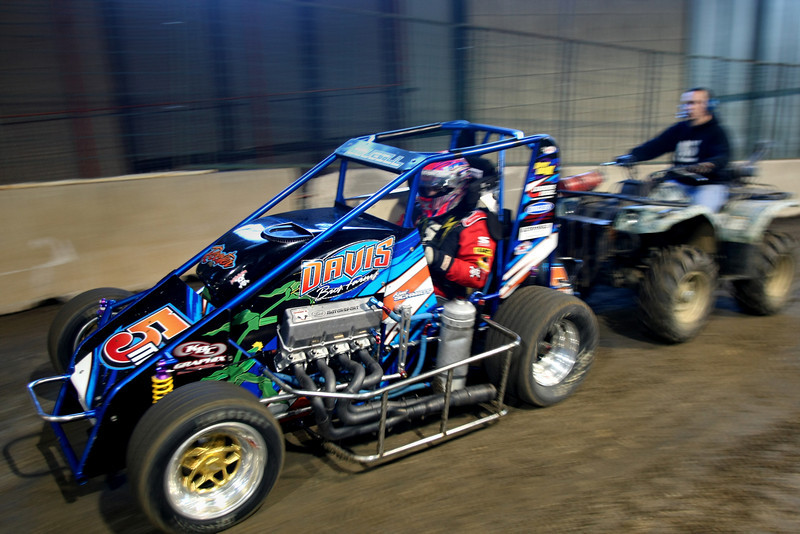 A crew member pushes race car to the starting grid at the Chili Bowl midget race Monday.  The week long racing event at the Tulsa fairgrounds brings millions of dollars of revenue into the Tulsa economy each year.