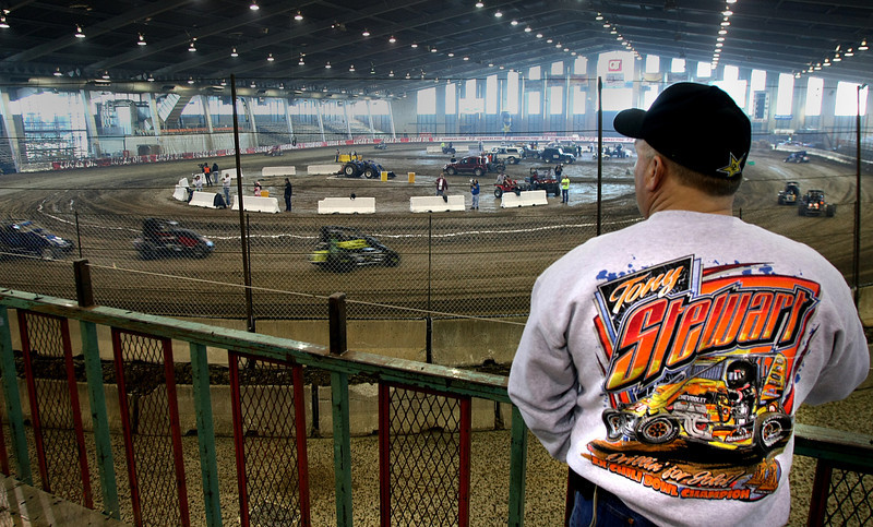 Sam Shannon of New Mexico watches midget race cars get in practice laps Monday at the Chili Bowl track.  The week long racing event at the Tulsa fairgrounds brings millions of dollars of revenue into the Tulsa economy each year.