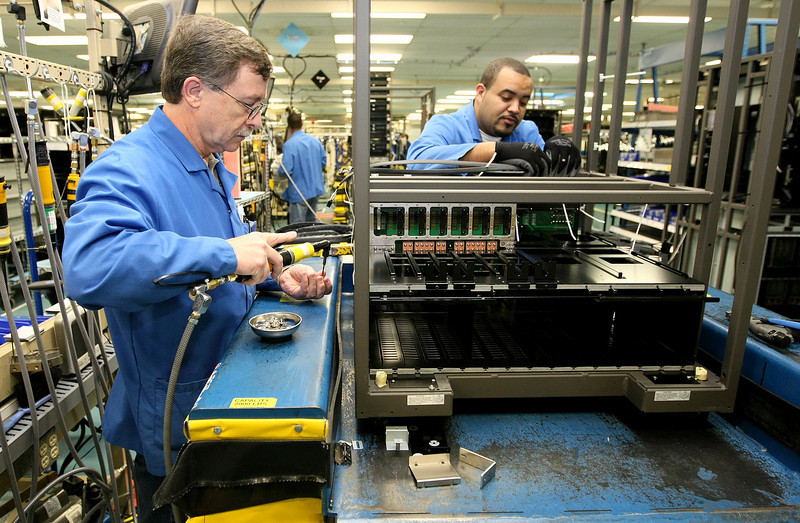 System assemblers Don Chadwick and Josh Nasbitt assemble a dkc unit at Hitachi Computer Products in Norman Monday. Hitachi has planned a 200,000 square foot expansion of its product line and is consolidating other services and bringing additional jobs. PHOTO BY MAIKE SABOLICH