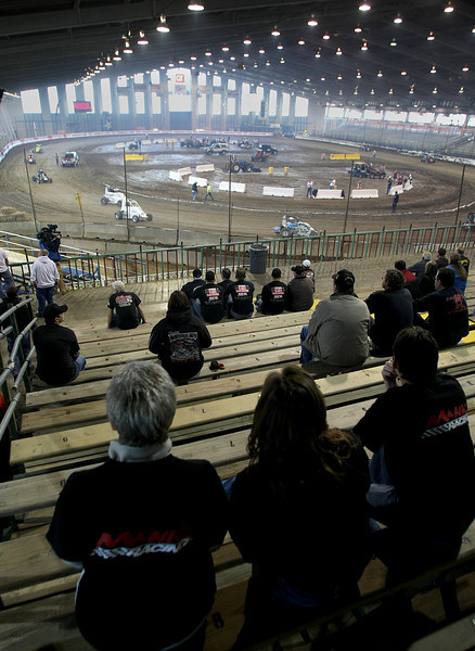Crew members watch as participants in the Chili Bowl race get in practice laps Monday.  The week long racing event at the Tulsa fairgrounds brings millions of dollars of revenue into the Tulsa economy each year.