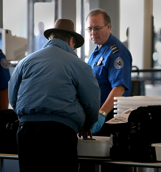 A TSA security officer assists a airline passenger through the security check at the Tulsa International Airport Friday.