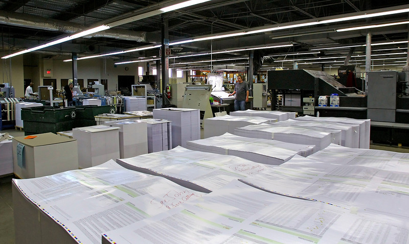 Thousands of newly printed direct mail pieces sit beside the presses at Resource One in Tulsa.