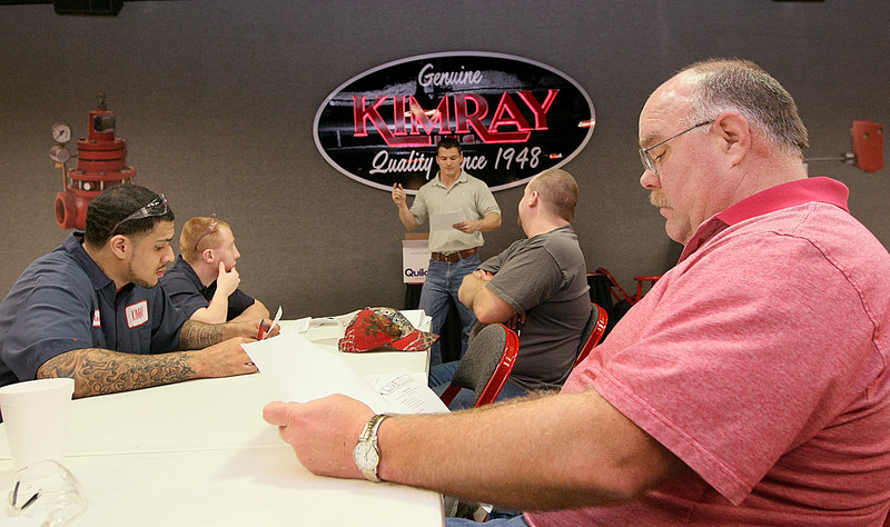 Rich Larsen, fleet supervisor at KimRay, right, and other KimRay employees learn how to earn points in a company-wide program that rewards healthy living choices with cash. PHOTO BY MAIKE SABOLICH