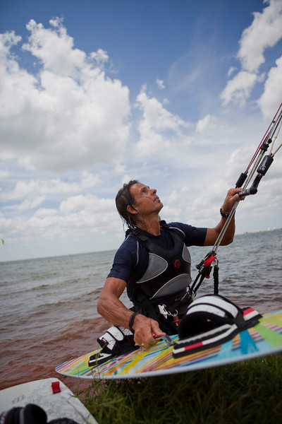 Kite surfer Jeff Shelley keeps a close eye on his kite while coming ashore to exchange surf boards. Shelley says Oklahoma's high wind makes ideal for inlan kite surfing. -PHOTO BY BRENT FUCHS