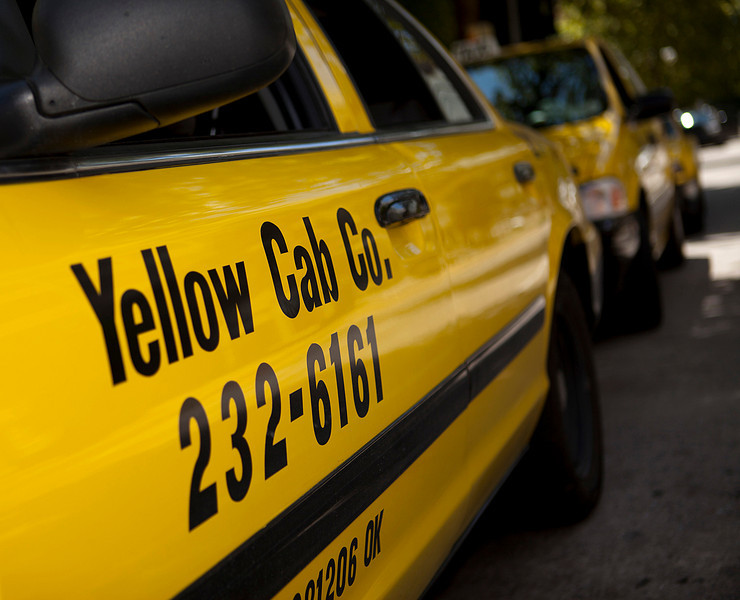 Yellow Cab Company taxis await fares along Main Street in downtown Oklahoma City. -PHOTO BY BRENT FUCHS