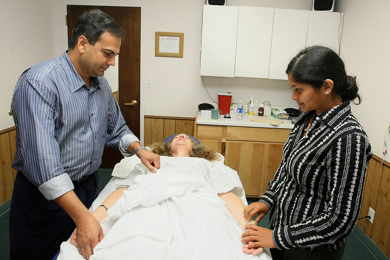 Dr. Amit Gumman and Dr. Richaritha Gundlapalli check on their patient Kay Evans before starting accupuncture therapy at Harmony Healing Center Tuesday. PHOTO BY MAIKE SABOLICH