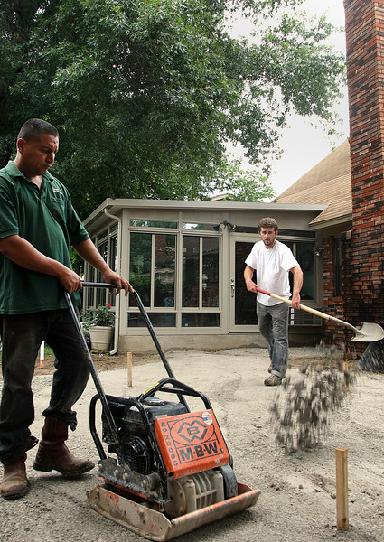 Workmen of Randol's Ponds and Landscapes work to install a backyard patio in Broken Arrow.