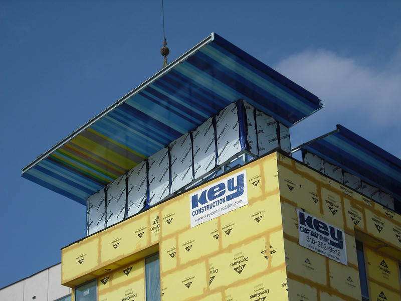 """A  """"Swoof,"""" a brightly colored metal roof that is a trademark of the Aloft Hotel brand, is part of designs for a hotel planned for downtown. Workers are installing a Swoof on an Aloft hotel in Tulsa in this picture."""