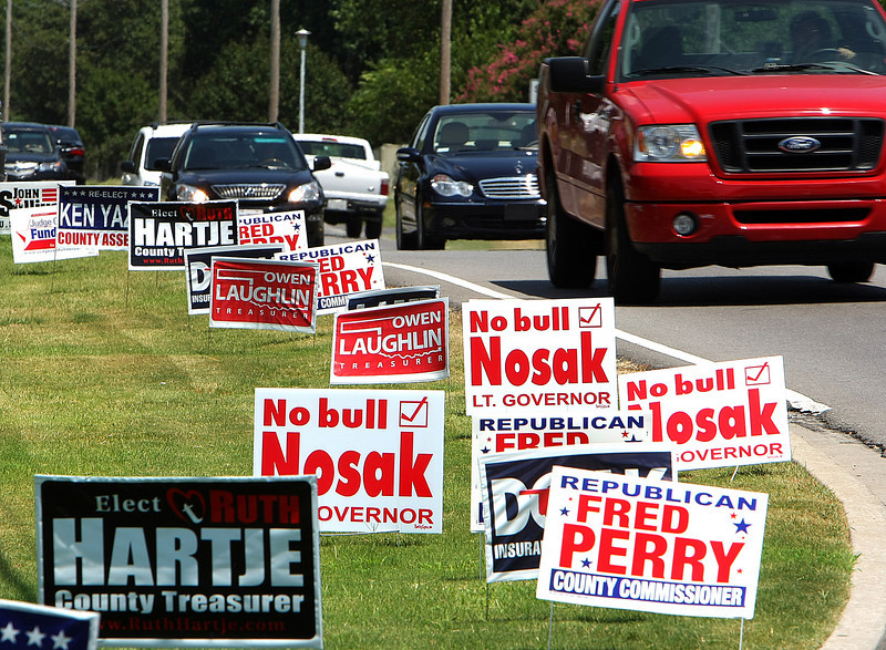 Motorists pass a few of the many candidate signs that appeared over the last week in Tulsa.