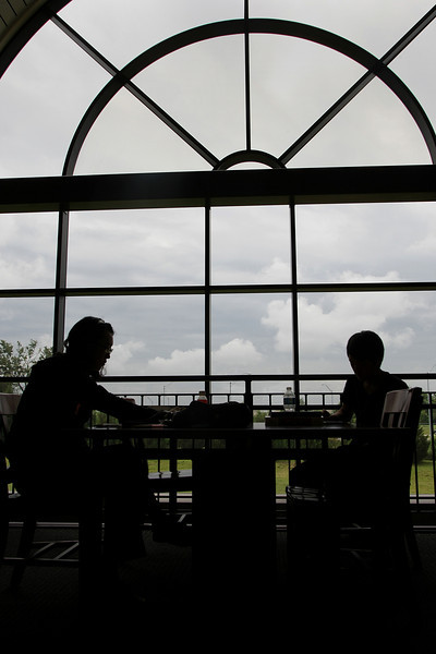 Two patrons are silhouetted against the one of the large windows of the Hardesty Regional Library in South Tulsa.