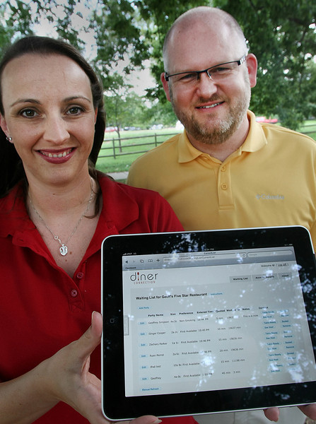Co-Founders of Moxie Software Shawna and Geoffrey Simpson, hold show an example of their newly created software allowing restaurants to page patrons on their cell phones when a table is ready.
