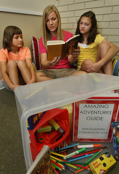 Sisters Kira and Anna Ziola are read a story by Seeking Sitters employee Annan Fullington.