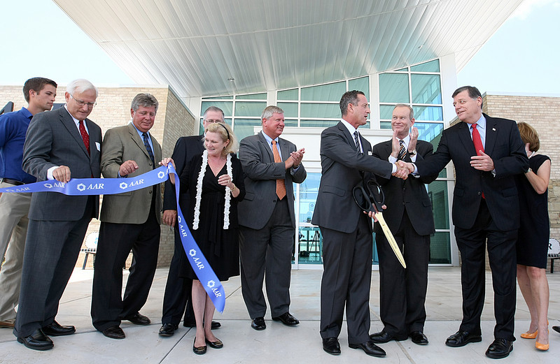 David Storch, CEO of AAR, shakers hands with Rep. Tom Cole, right, while Mayor Mick Cornett applauds after the ribbon cutting ceremony of the new corporate and general aviation facility at Will Rogers World Airport. PHOTO BY MAIKE SABOLICH