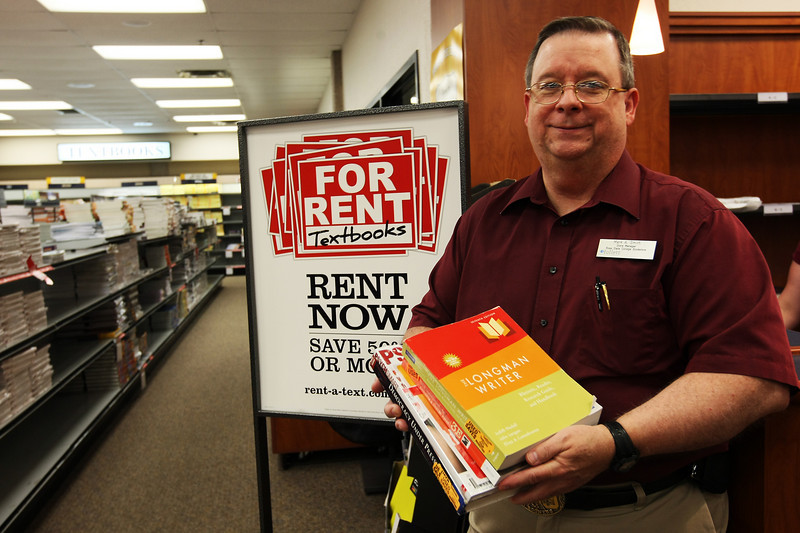 Mark Smith, manager of the Rose State Book Store stands with some of the books the store has recently began renting to students as an alternative to purchasing the books.
