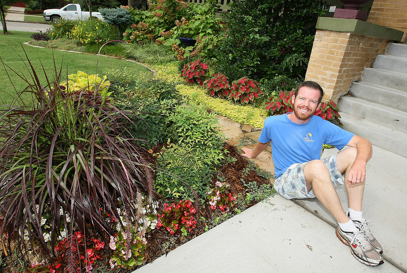 Landscape Artist Blake Emerson in a front yard on the corner of Shartel and 17th Street. PHOTO BY MAIKE SABOLICH