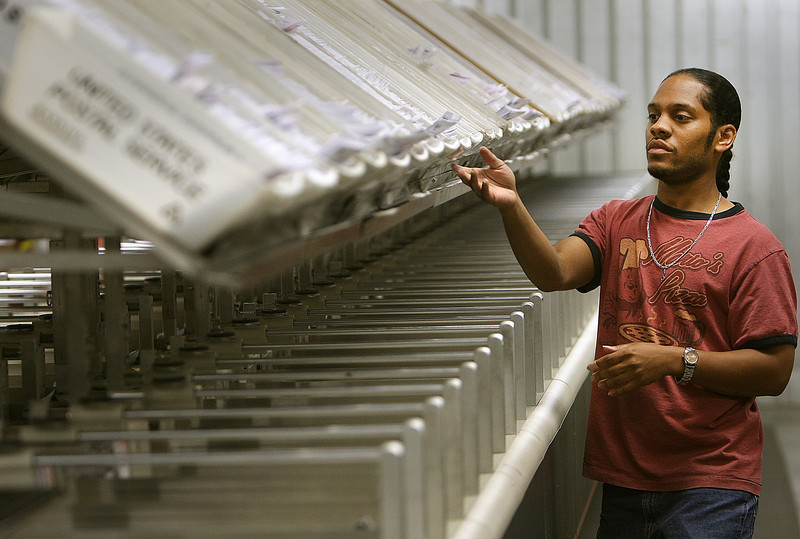 Anthony Alfred uses Automated Mail Service's Optical Character Reading sorter to mail and track clients pieces through the postal system.