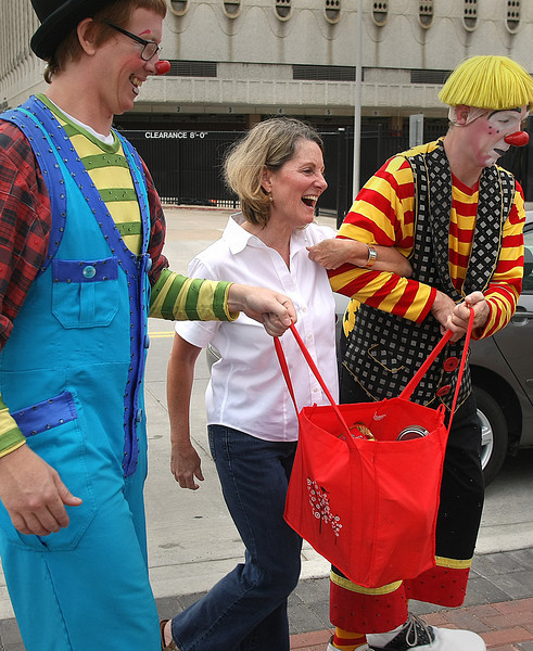 In downtown Tulsa Kerry Carlson is escorted to drop off food for the NE Oklahoma Food Bank by Ringling Bros. and Barnum and Bailey circus clowns.  The Circus is providing free tickets to the show for food donations.