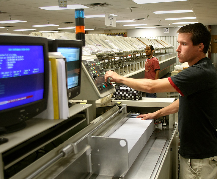 Anthony Alfred and Brian East use Automated Mail Service's Optical Character Reading sorter to mail and track clients pieces through the postal system.