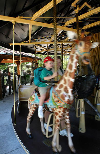 With a little help from his mother Jason Davis (2) gets a ride the carousel at the Tulsa Zoo Wednesday