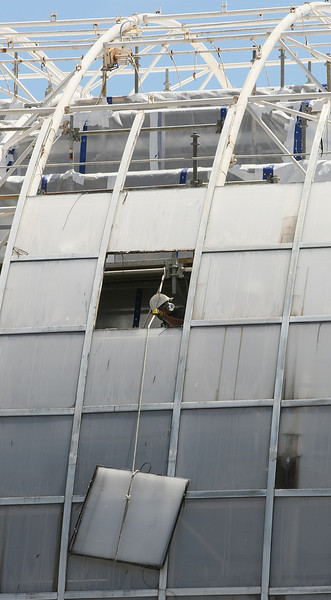 Construction worker lowers window panels out of the Crystal Bridge last week. PHOTO BY MAIKE SABOLICH