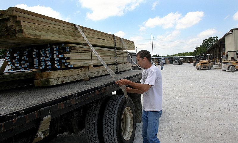 Thomas Compton straps the load he just picked up at Cedar Creek Lumber down for a trip to the job site Monday.