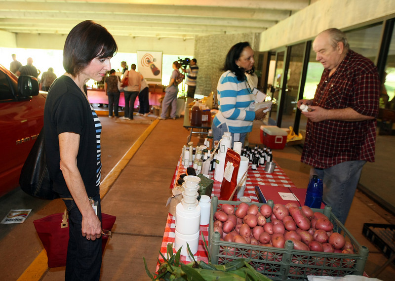 """Doris Carder, left, checks out fresh produce at the weekly """"Made in Oklahoma"""" Farmers Market at the Oklahoma State Health Department Friday. PHOTO BY MAIKE SABOLICH"""