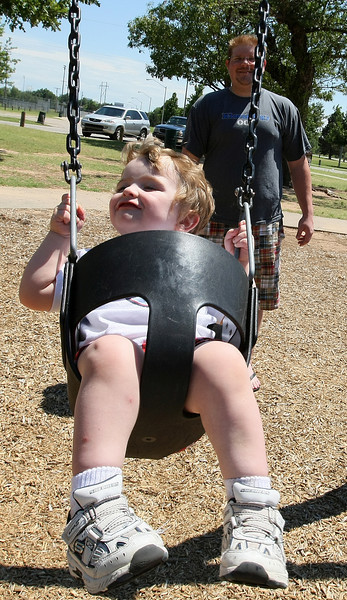 Two-year-old Bradley Moore enjoys himself on the swing set at Stars and Stripes Park Tuesday. Jopseph Blackburn stands behind him ready to push him forward. PHOTO BY MAIKE SABOLICH