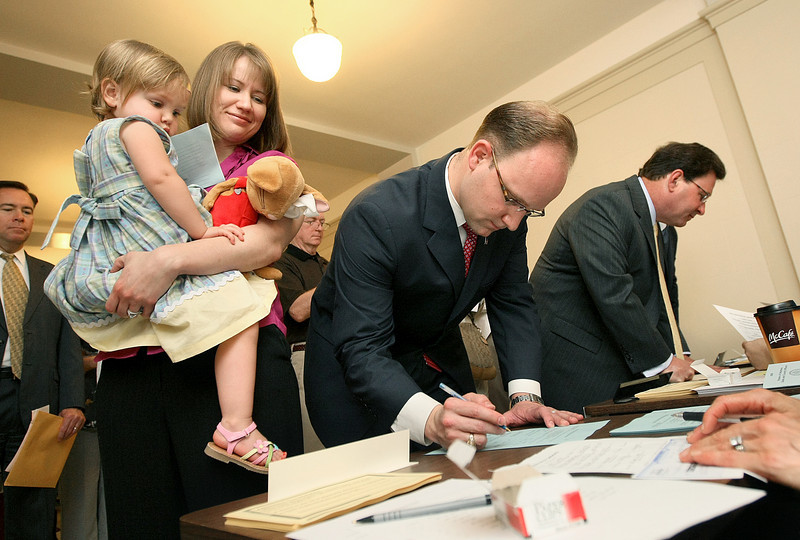 State Representative Scott Inman files for re-election at the State Capitol Monday as his wife Dessa and daughter Ellen are watching. PHOTO BY MAIKE SABOLICH