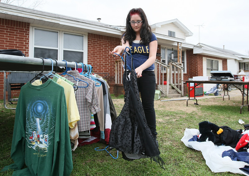 Justice Wisniewski puts clothes up for sale at a garage sale in Del City Monday. PHOTO BY MAIKE SABOLICH