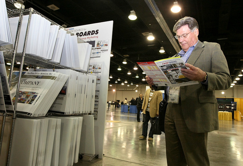 Independent Associate Jerry Pinneke browses through brochures at Fastsigns' booth at the Pre-Paid Legal Convention at Cox Convention Center Thursday. PHOTO BY MAIKE SABOLICH