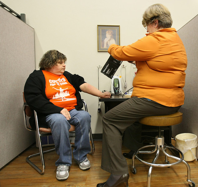 Glenna Warden is getting ready for Cathy Miller, director of clinical services at the Crossings Community Clinic, to take her blood pressure reading Friday. PHOTO BY MAIKE SABOLICH
