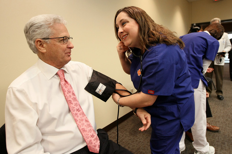 David Green, founder and CEO of Hobby Lobby, gets his blood pressure taken by medical assistant Laura Swope during the unveiling of theClinic, the company's new health and wellness center, Monday.  PHOTO BY MAIKE SABOLICH