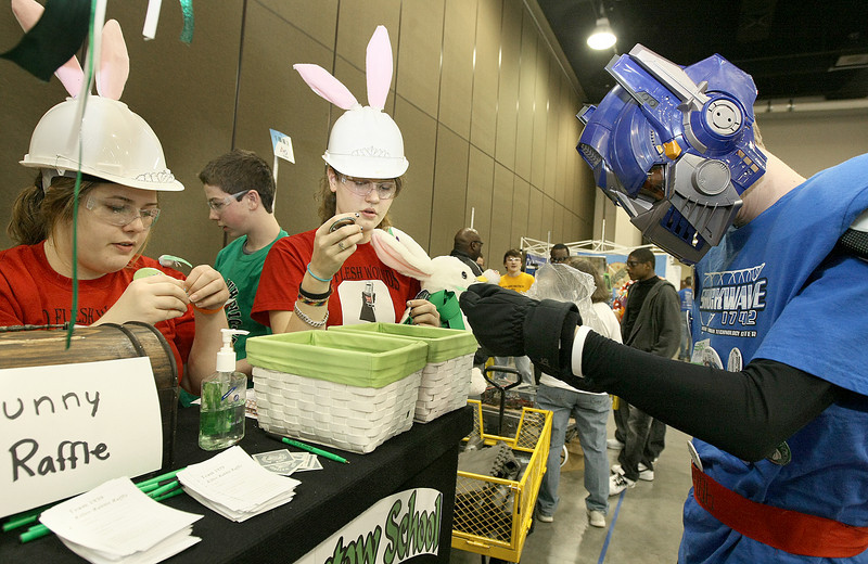Grace Guthrie, Bella Waldrop and Seth Sipe exchange their team's buttons during the Oklahoma regional FIRST Robotics Competition at the Cox Convention Center Thursday. PHOTO BY MAIKE SABOLICH