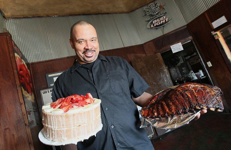 Charles Smith, owner of Leo's, at the restaurant's original location on 4rth and Harrison downtown with the strawberry bananan cake and a slab of ribs. PHOTO BY MAIKE SABOLICH