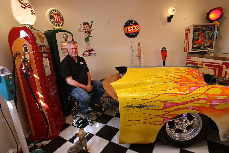 Michael Jones, Owner Gasoline Alley in Broken Arrow , sits in his office behind his desk made from the front of a classic car.