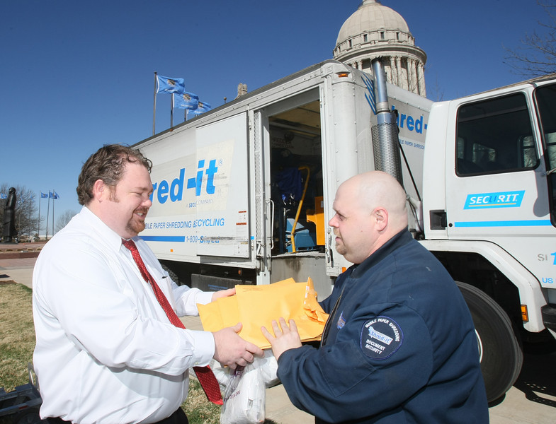 Anthony Sammons hands over his papers to be shredded to Jamie Hensley with Shred-it.  at the Capitol Tuesday. Free document shredding was provided as part of Consumer Protection Day all day by the Attorney General Scott Pruitt and Shred-it. PHOTO BY MAIKE SABOLICH