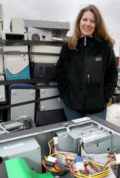 Traci Phillips, President/CEO of Natural Evolution in Tulsa, stands among the piles of used electronics her company recycles.