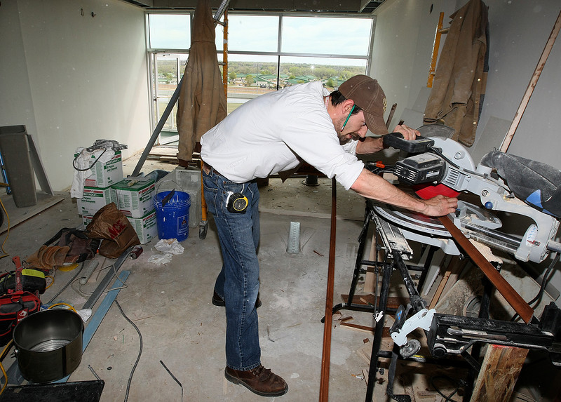 Trey Grimmett, carpenter with Midwest Commercial, works on new trim for a suite at Remmington Park Thursday. PHOTO BY MAIKE SABOLICH