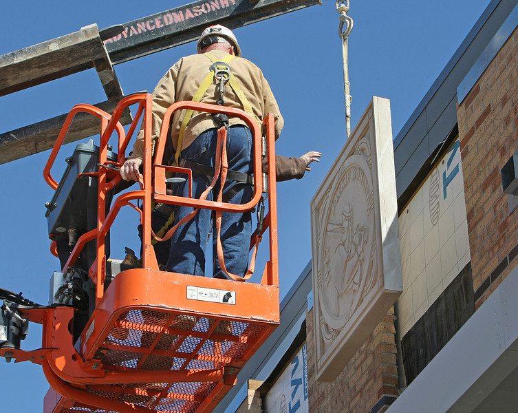 Workmen install a stone medallion commemorating Jackie Robinson into the façade of the OneOk ballpark in downtown Tulsa.