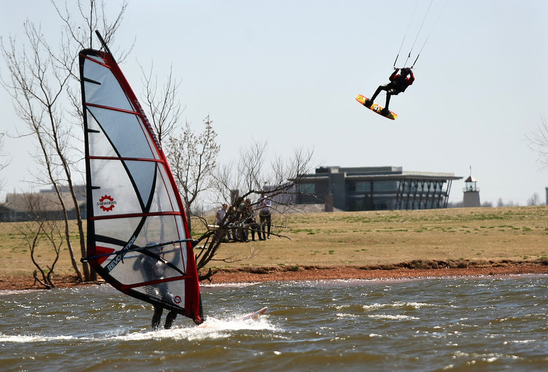 A surfer and a kite boarder enjoy the wind and the sun at Lake Hefner Wednesday. PHOTO BY MAIKE SABOLICH