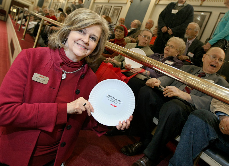 Nancy Coffer, state director of the AARP, holds up an empty plate in the Senate gallery. The AARP handed out empty plates Wednesday to to urge lawmakers to fund nutrition programs. PHOTO BY MAIKE SABOLICH