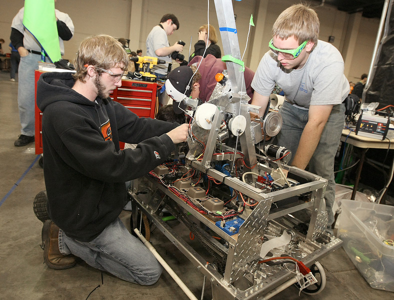 Clint Peck and Alex Scrudder work on team Crickets robot during the Oklahoma regional FIRST Robotics Competition at the Cox Convention Center Thursday. PHOTO BY MAIKE SABOLICH