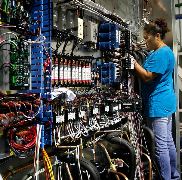 An Aaon employee works to intall a wiring harness on an industrial chiller at the companies Tulsa location.