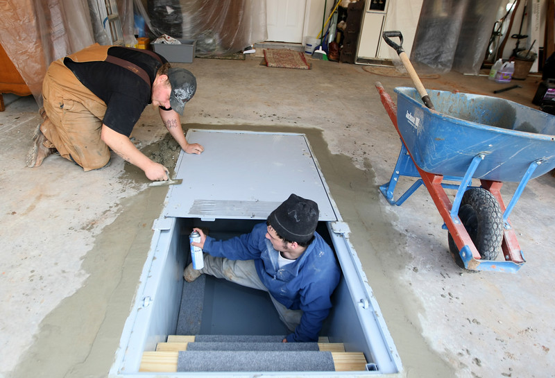 Cody Thibodeaux and Brandon Miller with Smart Safe Tornado Shelters are installing a storm shelter in a garage in Tuttle Wednesday. PHOTO BY MAIKE SABOLICH