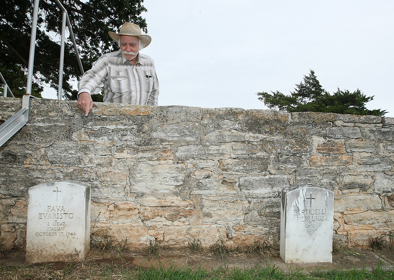 Bob Warren, visitor center director and secretary-treasurer of the board of Historic Fort Reno Inc., points to a grave of an Italion POW in a seperate section of Fort Reno's military cemetery. PHOTO BY MAIKE SABOLICH