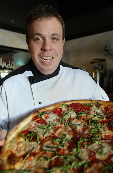 "Mike Bausch, Co-Owner of Andolini's Pizza in Owasso, works to prepare a  ""Pizza Amano"" pie.  The same pizza he entered in the World Pizza Championships in Salsomaggiore, Italy and placed in the top 20% with.  Bausch is opening a second shop on Cherry Street in Tulsa in August."